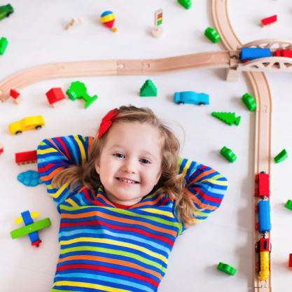 48147283 - child playing with wooden train, rails and cars. toy railroad for kids. educational toys for preschool and kindergarten children. little girl at daycare. view from above, kid playing on the floor.